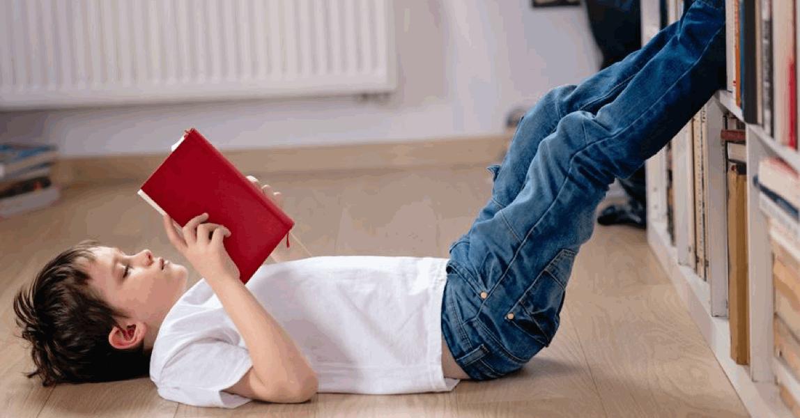 Jongen leest een boek op zijn rug op de vloer