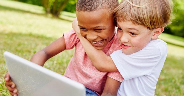 Jongens stoeien met een tablet buiten