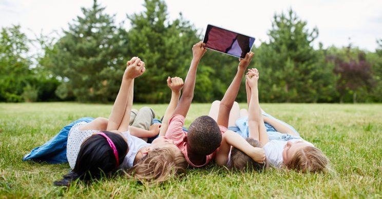 Kinderen liggen in het gras met een tablet