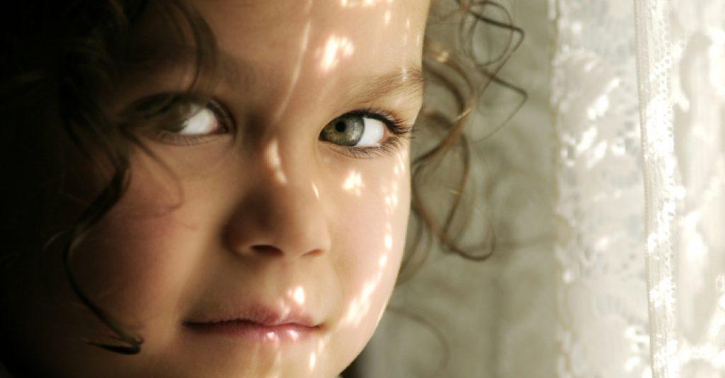 Meisje bij gordijn dat het zonlicht filtert