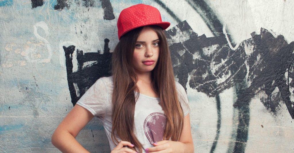Meisje met pet voor een muur vol graffiti