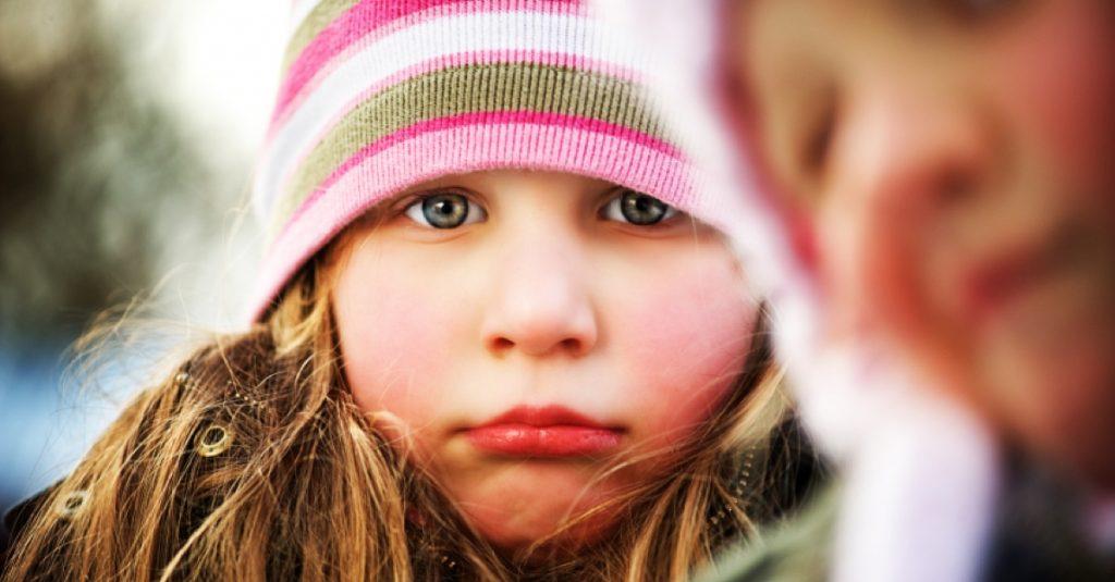 Meisje met muts kijkt sip in de camera
