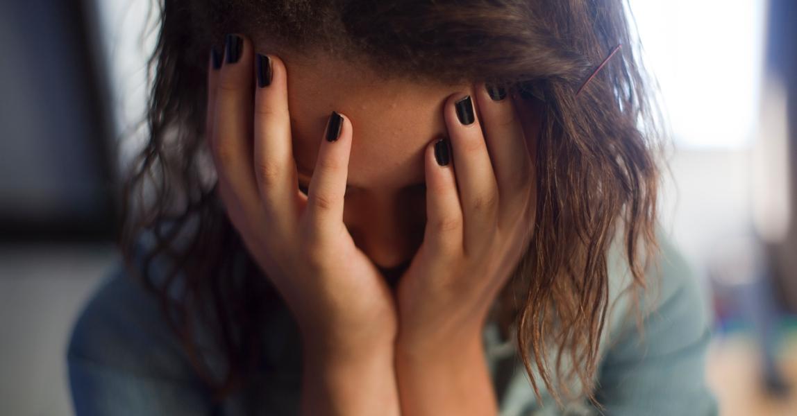Radeloos meisje met handen voor het gezicht