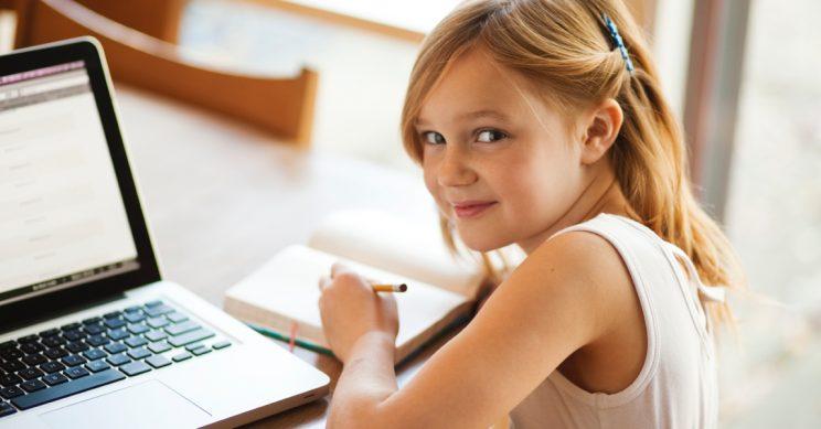 Meisje schrijft in een schrift naast een laptop