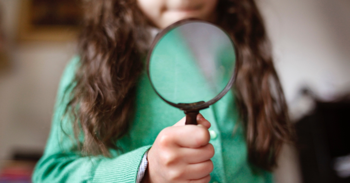 Meisje kijkt door vergrootglas