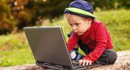 Peuter speelt met een laptop in het bos