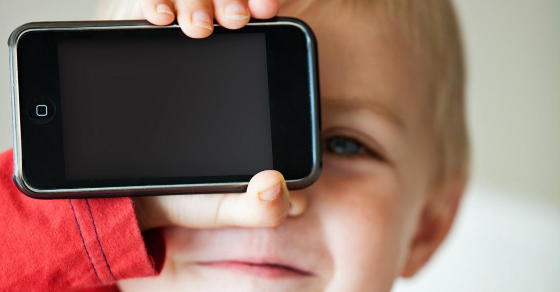 Peuter met smartphone voor zijn gezicht