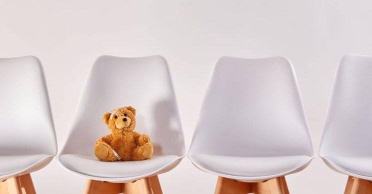 Teddybeer zit op een stoel in de wachtkamer