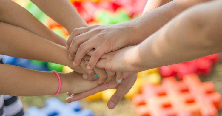 Kinderen leggen hun handen op elkaar