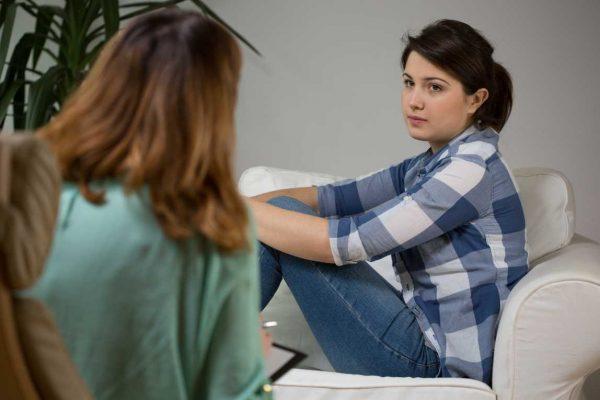 Jonge vrouw op de bank bij een therapeut