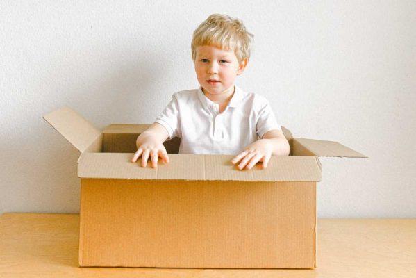 Jongen in kartonnen doos