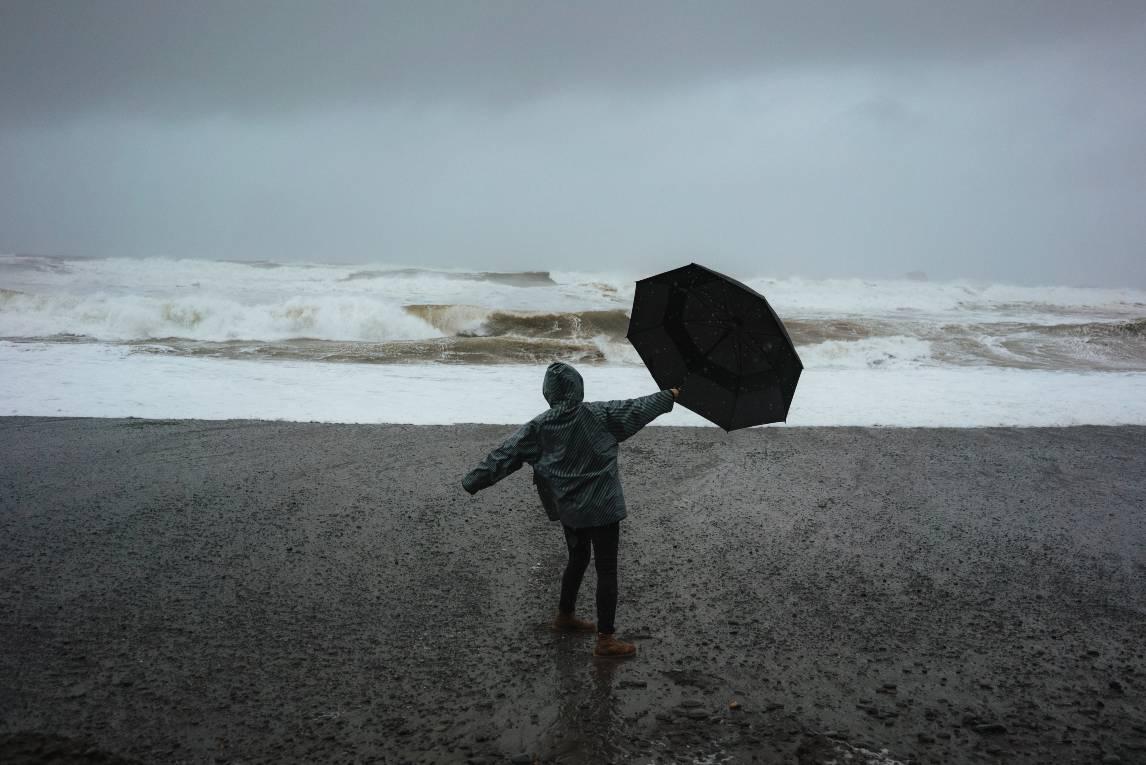 Iemand met een paraplu op het strand in de wind